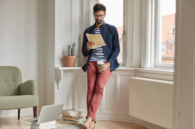 Volledige lengte shot van ernstige ongeschoren man of ondernemer studeert factuur, doet papierwerk thuis