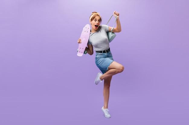 Volledige lengte shot van meisje in denim rok en shirt poseren met longboard. verlegen jonge vrouw in grijze outfit en witte moderne sneakers op zoek naar camera.