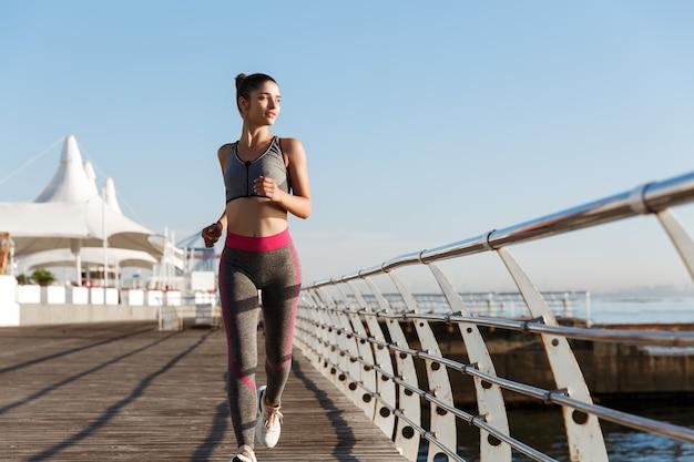 Volledige lengte shot van mooie en gezonde vrouw die langs de boulevard loopt en naar zee kijkt