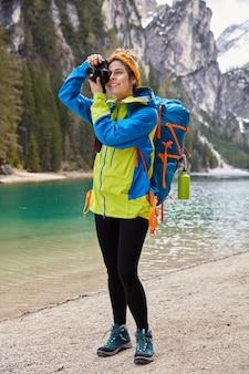 Volledige lengte shot van positieve fotograaf neemt foto van turquoise bergrivier, poseert op een prachtige plek voor toeristisch bezoek