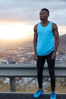 Volledige lengte shot van sportieve man draagt activewear, poseert bovenop met prachtig panoramisch uitzicht, geniet van sporttraining vroeg in de ochtend, mooie zonsopgang, heeft contemplatieve uitdrukking.