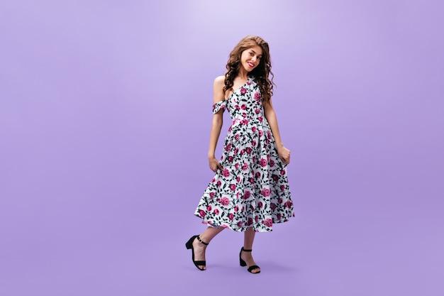 Volledige lengte shot van vrouw in bloemenprint jurk. charmante dame met golvend haar in lichte zomer outfit vormt op geïsoleerde achtergrond.