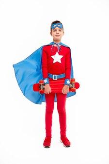 Volledige lengte sterke jongen in superheld kostuum met skateboard en camera kijken tegen wit