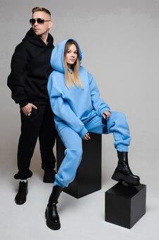 Volledige lengte stock foto van modieuze paar dragen zwarte en blauwe sportieve pakken van hoodie en joggers. meisje zittend op zwarte blokjes, man in zonnebril achter.