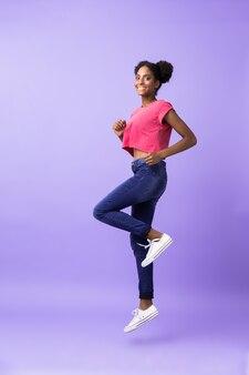 Volledige lengte tiener afro-amerikaanse vrouw glimlachend en rennen, geïsoleerd