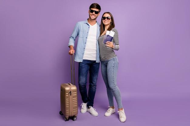 Volledige lengte twee mensen paar man dame wandelen luchthavenregistratie tickets paspoorten bagage vakantietijd dragen stijlvolle vrijetijdskleding geïsoleerde pastel paarse kleur muur