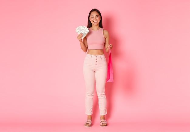 Volledige lengte van aantrekkelijk glimlachend aziatisch meisje in zomerkleding, met geld en boodschappentas, iets duurs kopen, genieten van wandelen in winkelcentra, staande roze muur