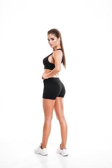 Volledige lengte van aantrekkelijke en geschiktheidsvrouw die achteruitgaat kijkt
