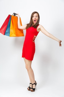 Volledige lengte van aantrekkelijke glamour blanke jonge bruinharige vrouw in rode jurk met multi gekleurde pakketten met aankopen na het winkelen geïsoleerd op een witte achtergrond. kopieer ruimte voor advertentie.