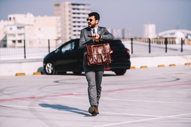 Volledige lengte van aantrekkelijke kaukasische bebaarde zakenman in pak met zonnebril met aktetas, wandelen op parkeerplaats en haasten om op tijd te komen op vergadering.