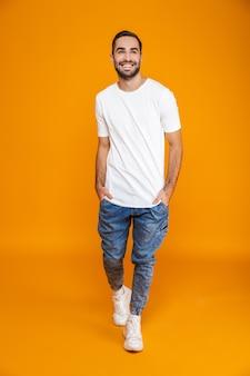 Volledige lengte van aantrekkelijke man in t-shirt en spijkerbroek lachend terwijl staande, geïsoleerd op geel
