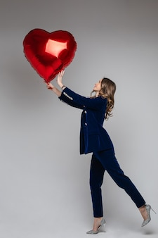 Volledige lengte van aantrekkelijke vrouw in blauw fluwelen pak met jasje en broek