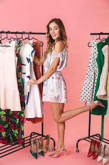Volledige lengte van aantrekkelijke vrouw in jurk staande in de buurt van garderobe met kleren en kiezen wat te dragen geïsoleerd op roze