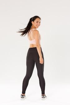 Volledige lengte van actieve en gezonde goed uitziende aziatische fitness meisje, sportvrouw draai achter op camera kijken met tevreden gezicht, sportschool coach moedigt start training, witte achtergrond.