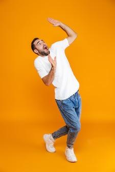 Volledige lengte van bange man in t-shirt en spijkerbroek die handen opheft terwijl hij staat, geïsoleerd op geel