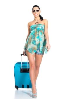 Volledige lengte van casual vrouw met reiskoffer