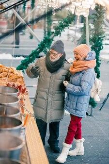 Volledige lengte van de stijlvolle gepensioneerden in winterkleren die voor de bakkersbalie staan en glimlachen