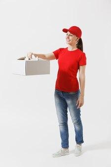 Volledige lengte van de vrouw in de rode dop, t-shirt die de cakedoos van de voedselbestelling geeft die op witte achtergrond wordt geïsoleerd. vrouwelijke koerier met dessert in ongemarkeerde kartonnen doos. levering dienstverleningsconcept. pakket ontvangen.