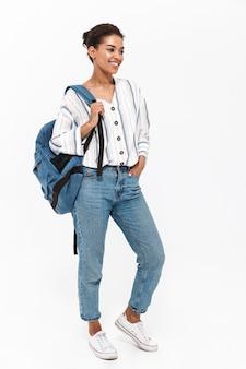 Volledige lengte van een aantrekkelijke jonge afrikaanse vrouw die vrijetijdskleding draagt die geïsoleerd over een witte muur staat en een rugzak draagt
