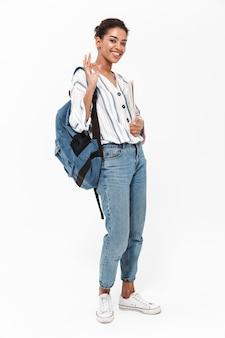 Volledige lengte van een aantrekkelijke jonge afrikaanse vrouw die vrijetijdskleding draagt die geïsoleerd over een witte muur staat, rugzak draagt, leerboek vasthoudt