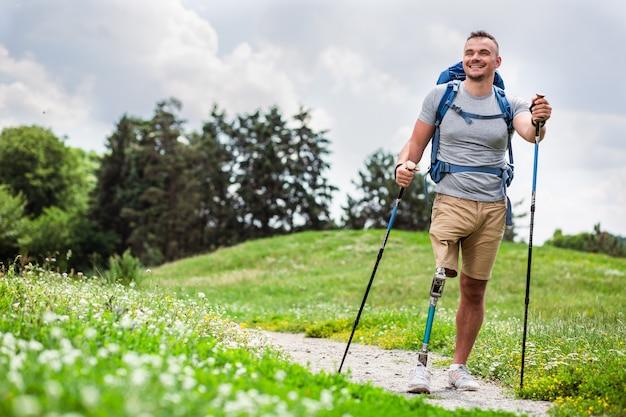 Volledige lengte van een aardige positieve jongeman met prothese die buiten loopt en geniet van zijn hobby