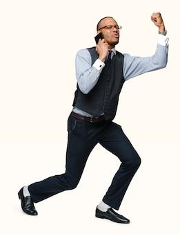 Volledige lengte van een afro-amerikaanse zakenman praten over de telefoon gebaren ja win geïsoleerd
