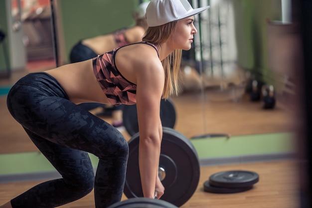 Volledige lengte van een fit jonge vrouw uit te werken met een halter in de sportschool. bodybuilderwijfje die bij de gymnastiek uitoefenen.