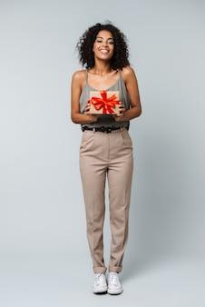 Volledige lengte van een gelukkige jonge afrikaanse vrouw terloops gekleed staande geïsoleerd, met een geschenkdoos