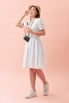 Volledige lengte van een gelukkige jonge vrouw die zich geïsoleerd over roze bevindt, die fotocamera houdt
