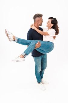 Volledige lengte van een gelukkige man die zijn vriendin vasthoudt terwijl hij geïsoleerd over een witte muur staat
