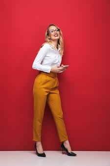 Volledige lengte van een gelukkige mooie jonge blonde vrouw die zich geïsoleerd over rode achtergrond bevindt, die mobiele telefoon houdt