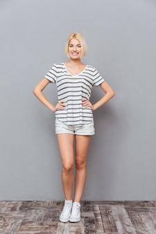 Volledige lengte van een gelukkige, mooie jonge vrouw die staat en glimlacht over een grijze muur