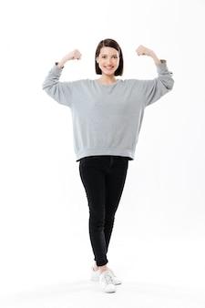 Volledige lengte van een gelukkige vrouw die en bicepsen bevindt zich toont
