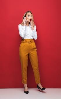 Volledige lengte van een geschokte mooie jonge blonde vrouw die zich geïsoleerd over rode achtergrond bevindt, die mobiele telefoon houdt