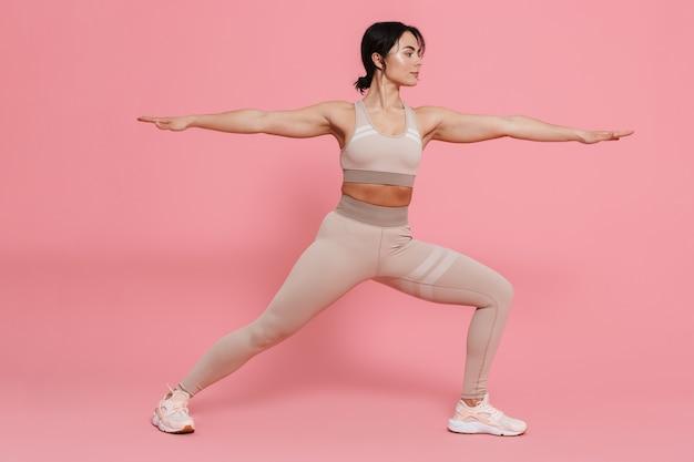 Volledige lengte van een gezonde, fitte jonge vrouw die sportkleding draagt en rekoefeningen doet die over roze muur zijn geïsoleerd