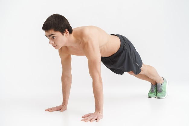 Volledige lengte van een gezonde fitte sportman die plankoefeningen doet over wit
