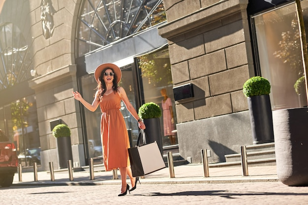 Volledige lengte van een jonge, gelukkige modieuze vrouw met boodschappentassen in een lange zomerjurk en schoenen met hoge hakken die buiten op de weg staat, wachtend op een taxi. winkelen, mensen levensstijl concept