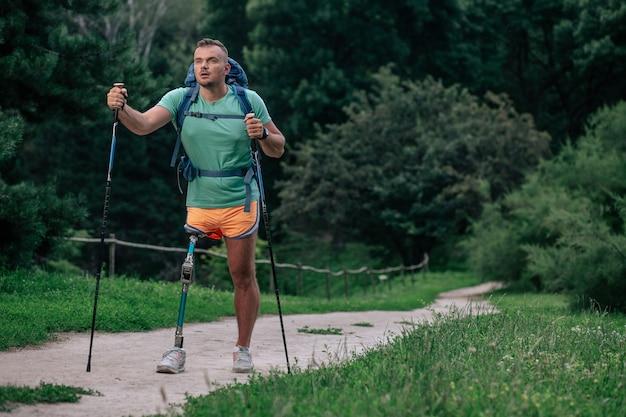 Volledige lengte van een jonge sportieve man met prothese die buiten tijd doorbrengt terwijl hij nordic walking probeert