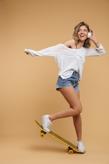Volledige lengte van een mooi jong meisje met een koptelefoon op een skateboard dat over een gele muur wordt geïsoleerd