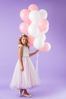Volledige lengte van een mooi klein meisje gekleed in prinsessenjurk staande geïsoleerd over violette muur, met bos ballonnen