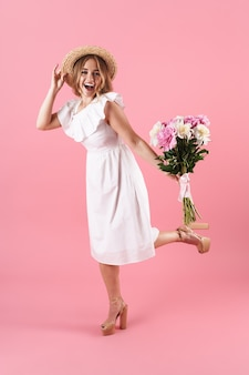 Volledige lengte van een mooi vrolijk jong blond meisje met een zomerjurk die geïsoleerd staat over een roze muur, een boeket pioenrozen vasthoudt, poserend