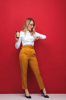 Volledige lengte van een mooie jonge blonde vrouw die geïsoleerd over rode achtergrond, afhaalmaaltijdenkoffie houdt, tijd controleert
