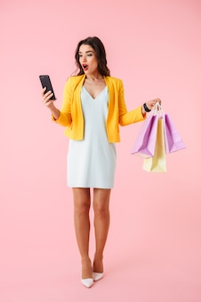 Volledige lengte van een mooie jonge vrouw die kleurrijke kleren draagt die zich geïsoleerd over roze bevinden, het dragen van boodschappentassen, met mobiele telefoon