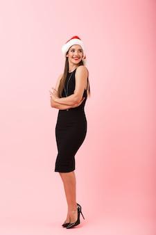 Volledige lengte van een opgewonden jonge vrouw met kerstmuts vieren geïsoleerd op roze achtergrond, wegkijken