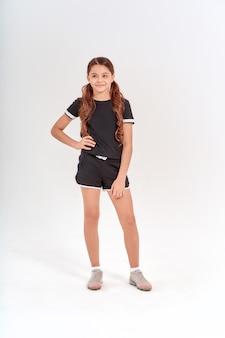 Volledige lengte van een schattig tienermeisje in sportkleding dat naar de camera kijkt terwijl ze geïsoleerd over grijs poseert