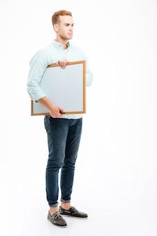 Volledige lengte van een serieuze roodharige jongeman die een whiteboard vasthoudt