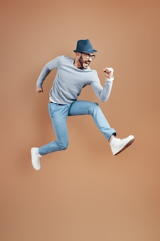 Volledige lengte van een speelse jongeman in vrijetijdskleding die schreeuwt en gebaart terwijl hij tegen een bruine muur zweeft