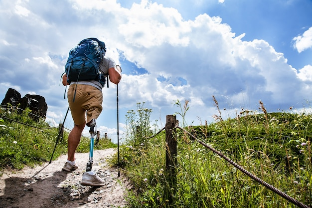 Volledige lengte van een sportieve jongeman met prothese die langs het pad loopt terwijl hij nordic walking-stokken gebruikt