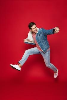 Volledige lengte van een vrolijke jonge man met een warm spijkerjack die geïsoleerd over rode muur springt, een selfie neemt