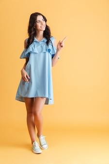 Volledige lengte van een vrolijke mooie vrouw in blauwe jurk die vinger wegwijst